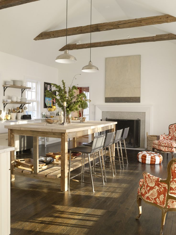 I love this unique open space for a kitchen: hardwood floors, vaulted ceiling with beams, huge butcher block island, open shelves, long pendant lights, and the unique seating area