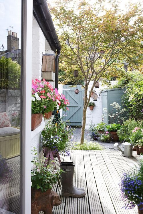 Pretty decking, pots and lanterns in Nic Guymer and Dave Turner's London garden
