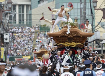 Men pull a huge wooden float at high speed through the streets of Kishiwada in Osaka Prefecture during the Kishiwada Danjiri Festival on Saturday. Thirty-four floats, each weighing 4 tons, took to the streets when the annual two-day festival opened the same day | The Japan Times Online