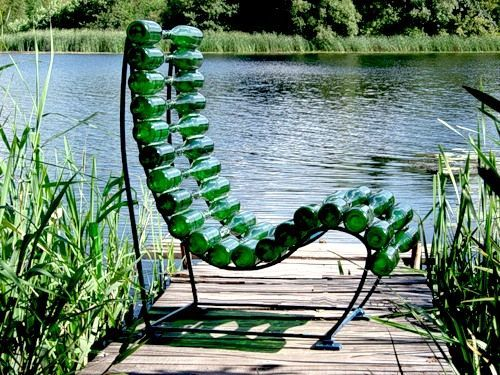 """Chair made from bottles. Funny chair made from green bottles and places on footbridge near beautiful lake.The chair's frame is made from metal but the bottles is in woods place. This chairs is not very effective but stylish.  Ouch, I wouldn't trust sitting on that! ٩(͡๏̯͡๏)۶ Sure is """"glassy"""" though."""