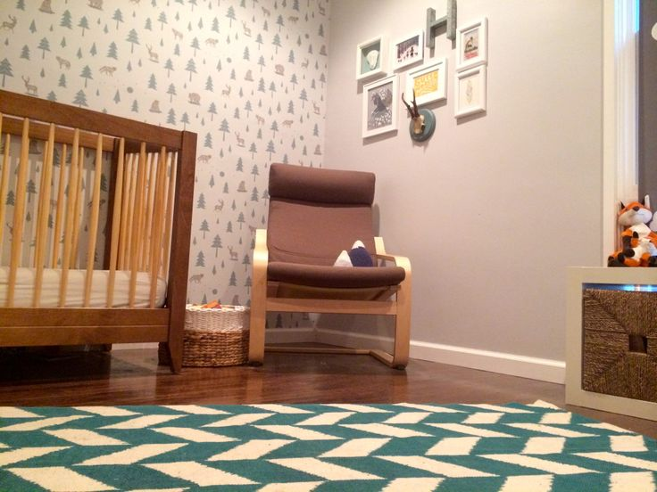 This modern alpine-themed nursery features a wallpaper accent wall and a fab herringbone rug from @Urban Outfitters!
