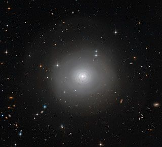 This image of PGC 10922, an example of a lenticular galaxy — a galaxy type that lies on the border between ellipticals & spirals. Seen face-on, this image shows the disc & tightly-wound spiral structures of dark dust encircling the bright centre of the galaxy. There is also a remarkable outer halo of faint wide arcs or shells extending outwards. These are likely to have been formed by a gravitational encounter or even a merger with another galaxy.