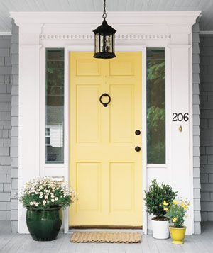 a happy yellow door with black wrought iron accessories