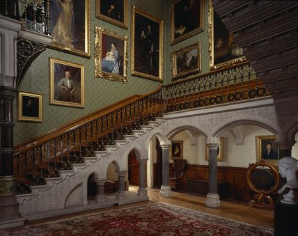The Main Staircase at Tyntesfield, viewed North West across the Hall, with a carved iron work banister and arched stone supports and family portraits on the walls