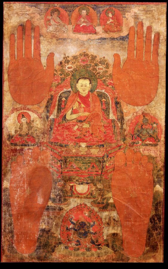 Lama:  Attired in the orange and red robes of a monk sits on a throne. Lrft is the bodhisattva of long-life, White Tara, and on the right Green Tara. Above and below are the red hand and foot prints of the lama. Top center is Marpa the Translator. Left - Yogi Milarepa. Right-  student Gampopa. Bottom center Shadbhuja Mahakala, the wrathful enlightened Dharma protector, with one face and six hands surrounded by orange flames.