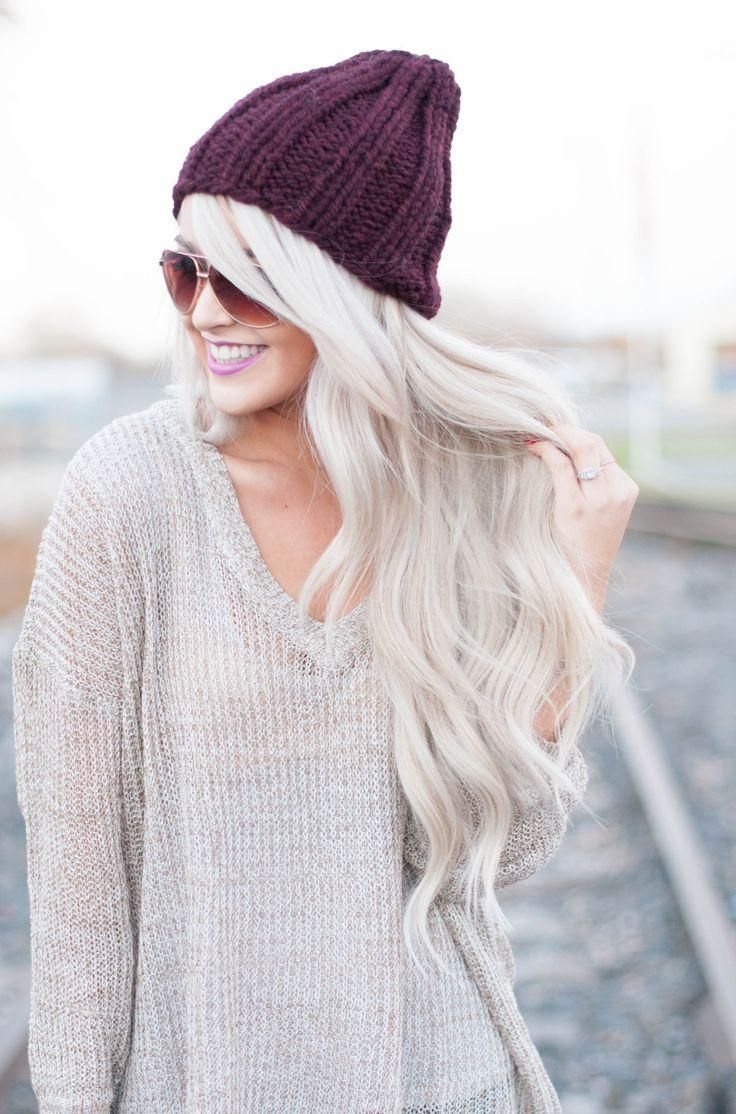 Beanie and an oversized sweater with long platinum blonde waves.