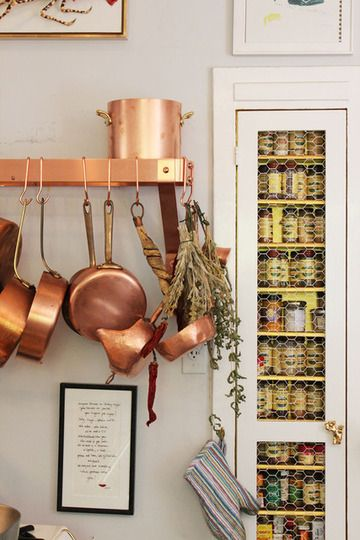 copper pots and spice storage cabinet.