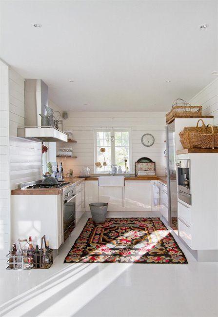 open white kitchen. butcher block countertops. multicolored rug.