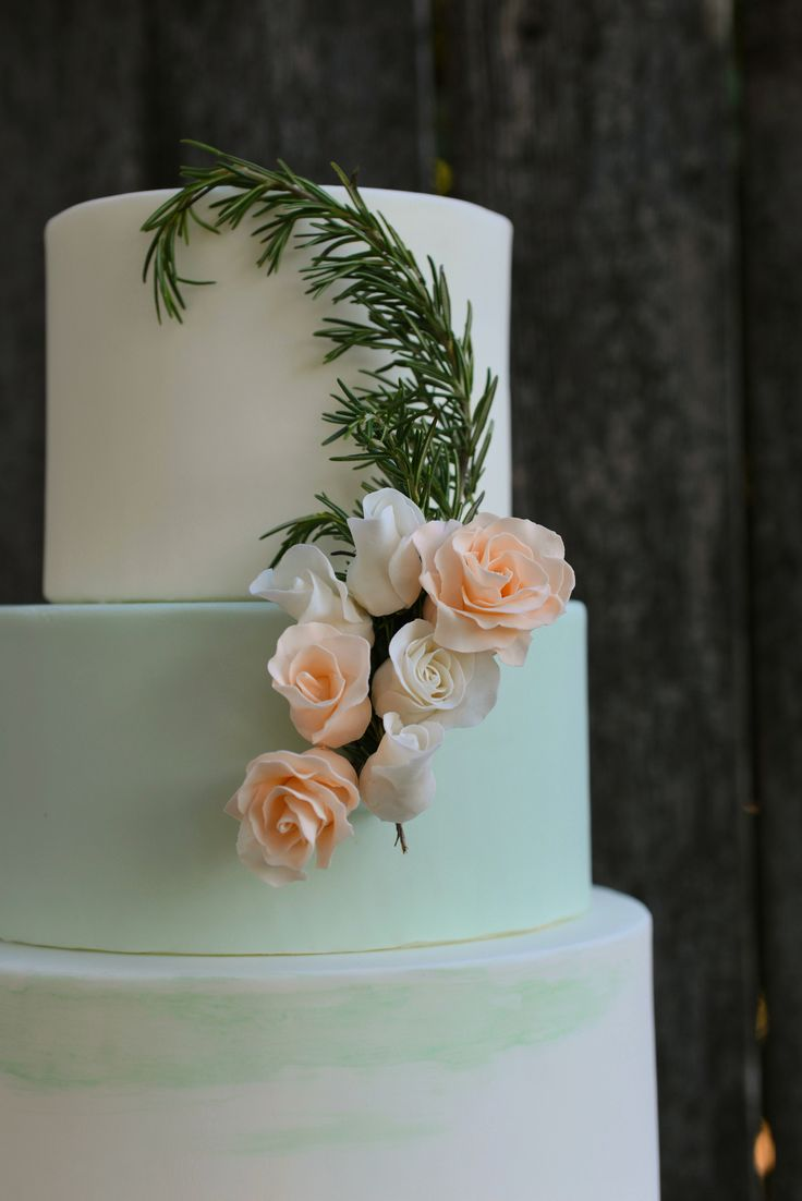 cake in white and mint with white and peach sugar flowers and rosemary ...