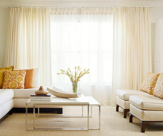 creamy white walls and window treatments are the backbone of this clutter-free room. Furniture with clean lines sticks with the streamlined look. A modern nesting table pulls out for serving food and drinks. To maintain the crisp look, pick a single accent color in a modern shade, like bright orange. Replace with a new hue to change the look.
