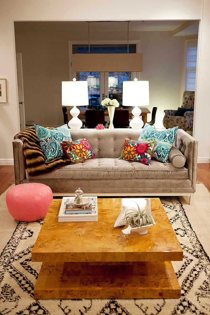 velvet couch, bright pillows, patterned rug.