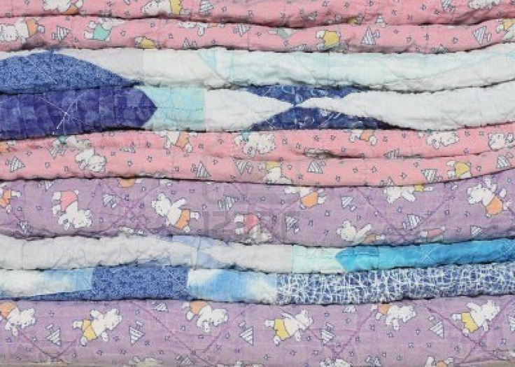A stack of faded, fraying and worn handmade purple, blue and pink children's quilts.