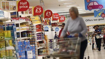 A customer pushes a shopping cart past signs displaying goods at reduced, buy one get one free (BOGOF), or half-price, inside a Tesco Extra ...