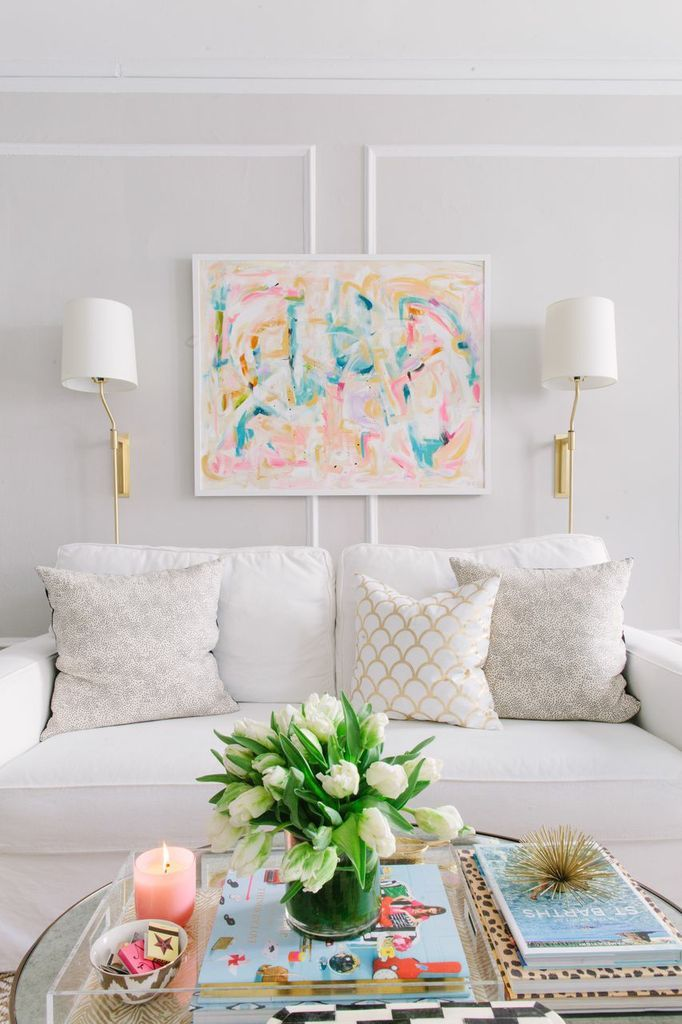 @Danielle Lampert Lampert Moss Chicago Home Tour // living room // white couch // pink and gold // @Vicki Smallwood Snyder Barn white sofa // Aurelia throw pillows // @Caitlin Burton Burton Wilson Textiles gold throw pillows // Cocoa and Hearts painting // @Lucy Kemp Chavez Style Lighting wall sconces // @Karen Jacot Crump Designs side tables // @Toni Williams Studio gold elephant // photography by Stoffer Photography