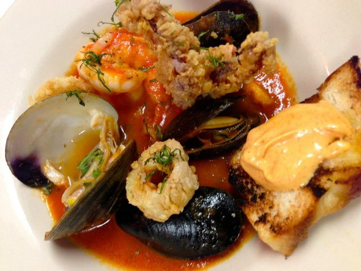 ... with clams, mussels, rock shrimp, squid in tomato saffron confit