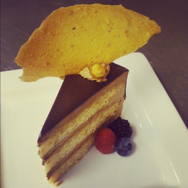 Chocolate hazelnut cake topped with hazelnut tuile and fresh berries