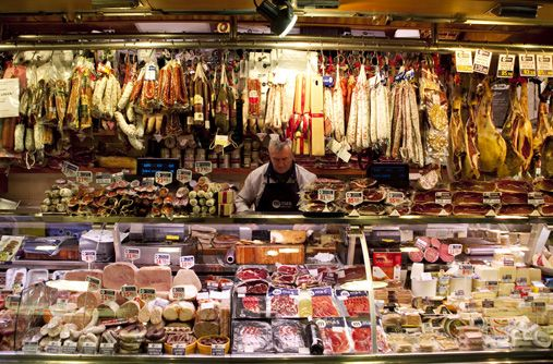 A butcher, one of many vendors at La Boqueria Market, prepares meat behind the counter.