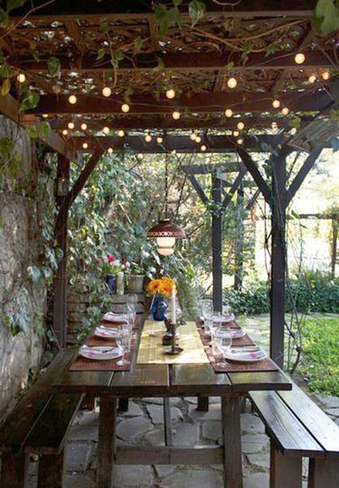 Rustic covered outdoor dining space: simple table and lights add to the cozy feel of this space