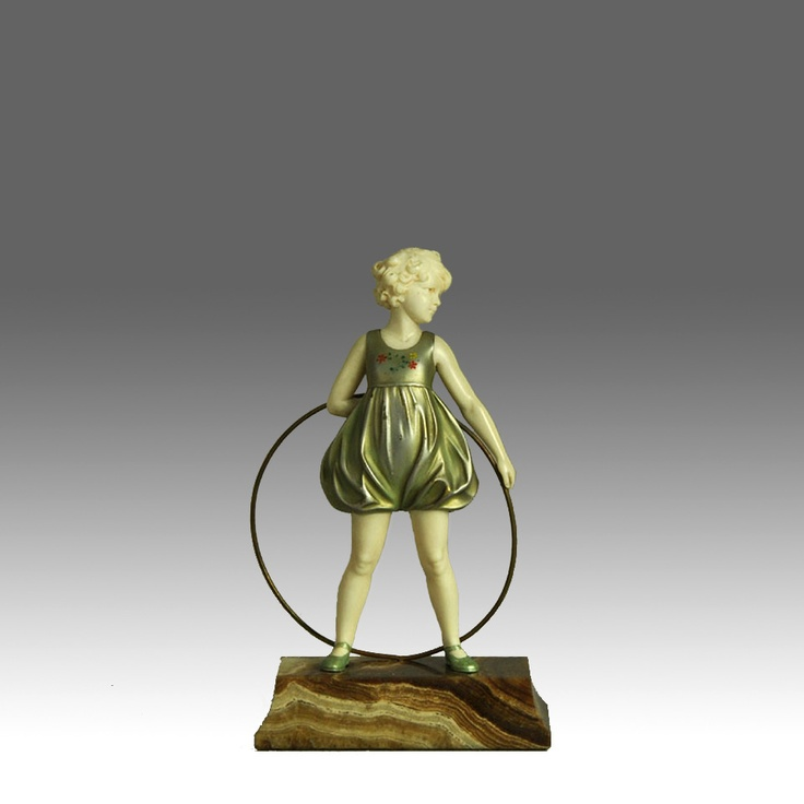 A superb early 20th Century chryselephantine (bronze and ivory) figure of a young girl holding her hoop behind her back.  Raised on a shaped brown onyx plinth, with excellent detail and colour, signed.