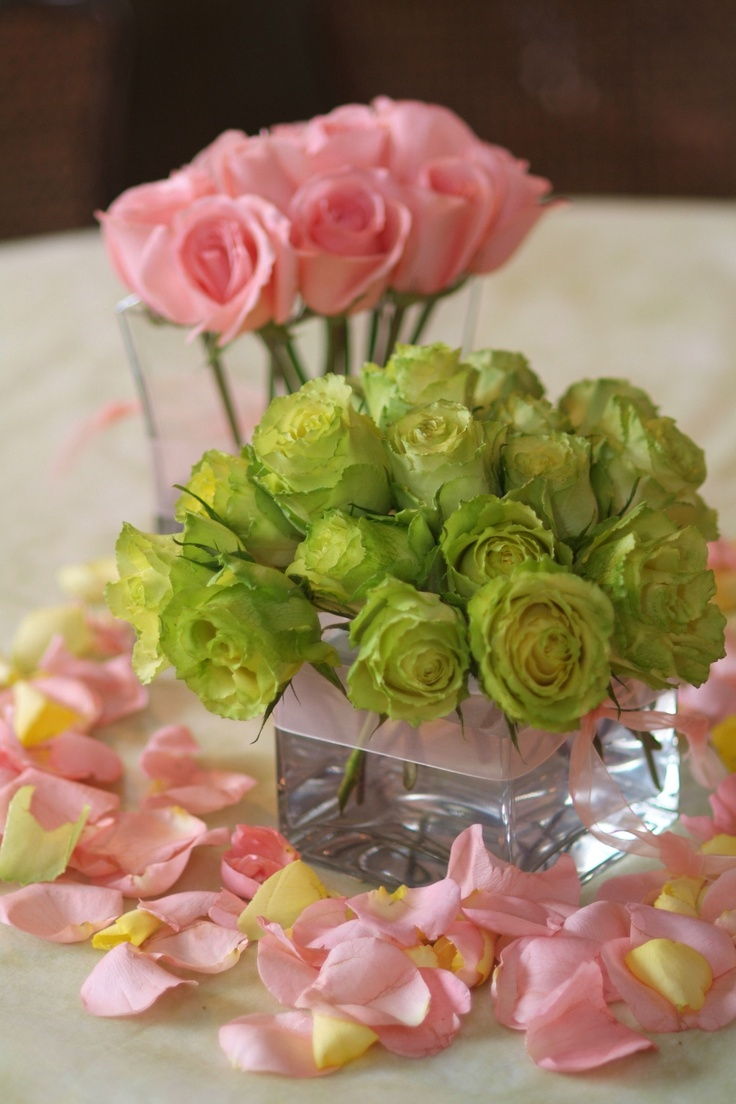 square glass cube with green and peach roses and a scattering of petals
