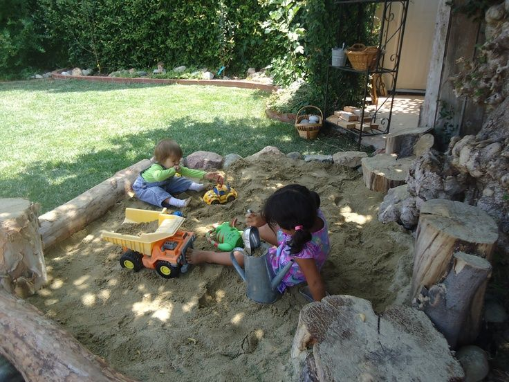 sand play area under tree  Logs and rocks sand box under tree shaded