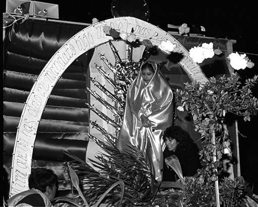 Diana del Toro, a member of the Santa Rosa Catholic Church Youth Group, plays the part of the virgin at the Santa Rosa Catholic Church Guadalupe Festival, December 12, 1987. Del Toro is accompanied by her aunt, Elisa Flores. Robert and Betty Franklin Collection. San Fernando Valley History Digital Library.