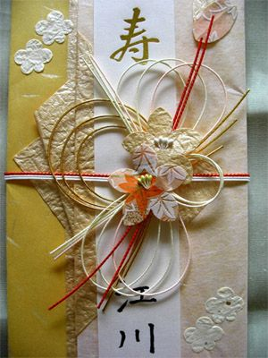 Paper cord, paper flowers, embossed paper.  A Japanese folded paper envelope to hold a gift of money.