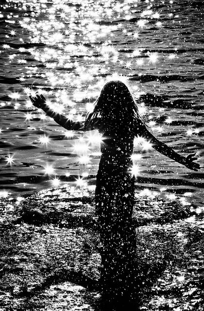 Black and white image of a girl playing in the sea. Love the atmosphere the photographer has captured.