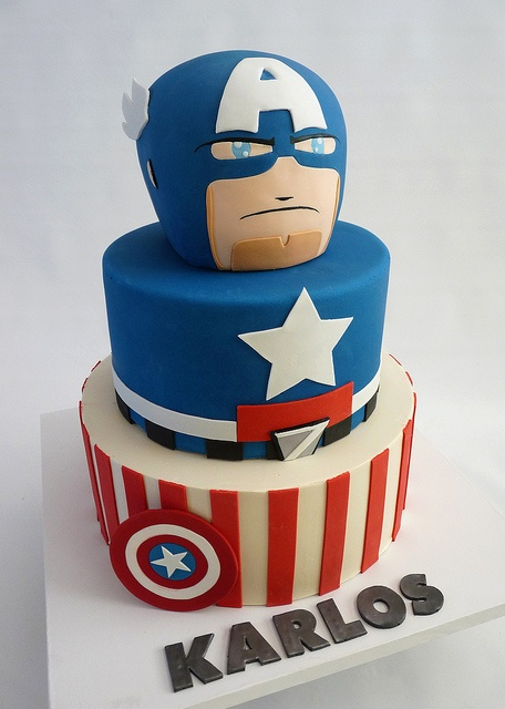 A Captain America Cake  Bottom tier iced in buttercream. Top two tiers covered in fondant. Gumpaste, and fondant accessories.