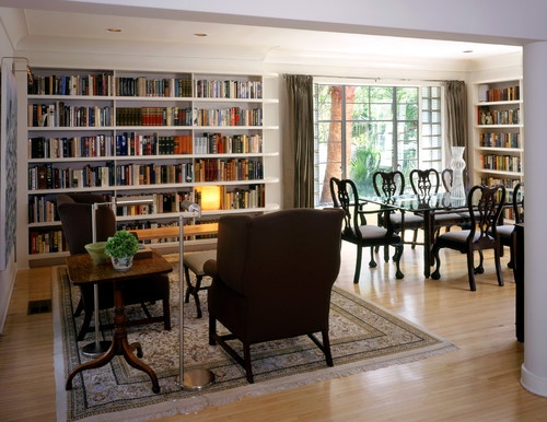 Two perpendicular walls are covered with books in this room, separated by a large window that brings in plenty of daylight. Note how the shelves are rounded at the window, a nice Art Deco touch.