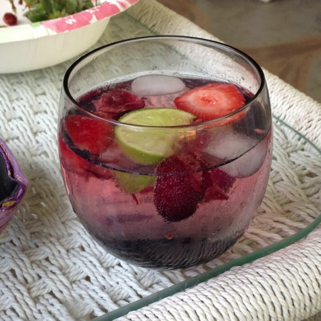 Vodka tonic with cherries, strawberries, and a lime wedge.