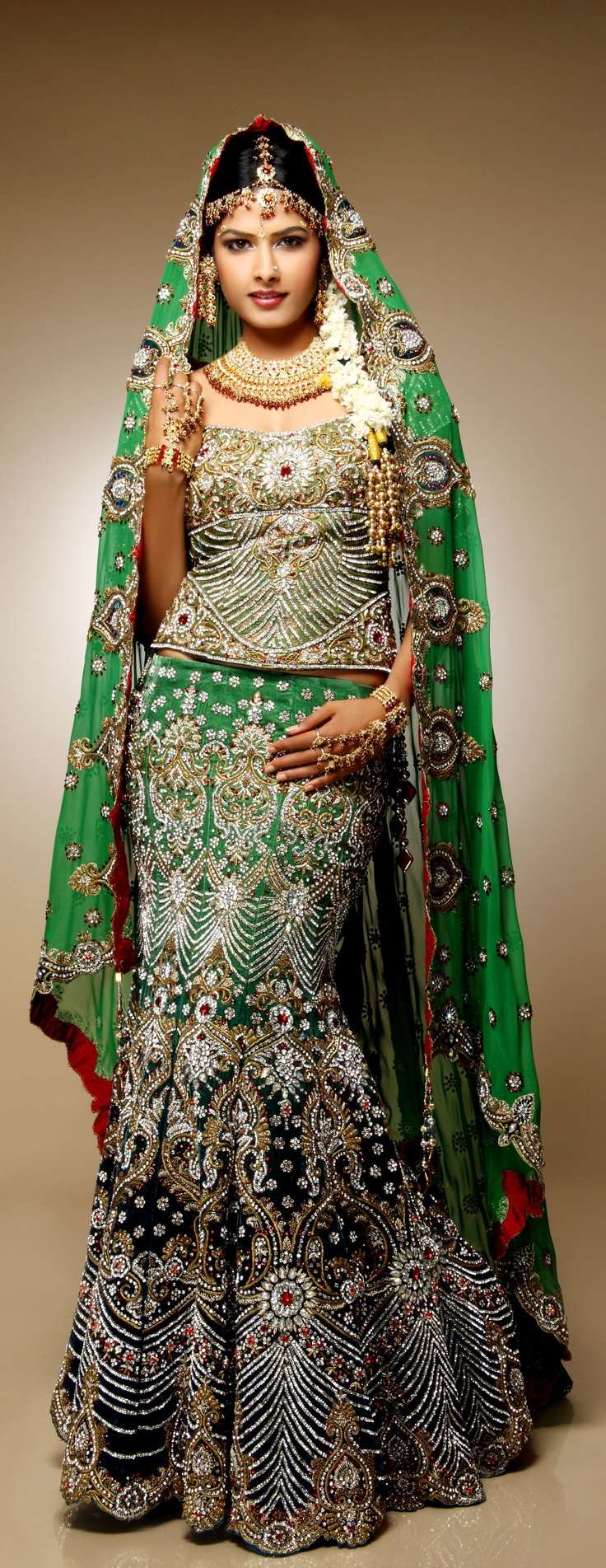 Velvet lehenga, which has a unique blend of green and deep teal blue, is made using georgette dupion with teal blue velvet. It is finished with maroon raw silk and has a heavily clustered butti of kundan, Swarovski and maal on the dupatta.
