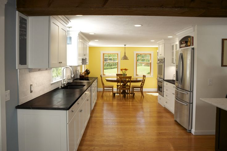 White Open Floor Kitchen And Yellow Dining Room With White Cabinet And