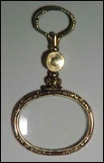 """Gold quizzing glass with locket in handle. Lens surround is alternately chased and plain, with an inner ring of twisted rope design. Handle of floral-chased ball and engined-turned round locket that opens to show woven hair beneath a glass cover. Swivel-mounted loop echoes decoration of lens outer surround. Oval magnifying lens. 3 ¼"""" long. c1815."""