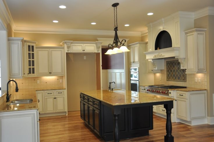 Breathtaking antique white linen cabinets with black distressed island