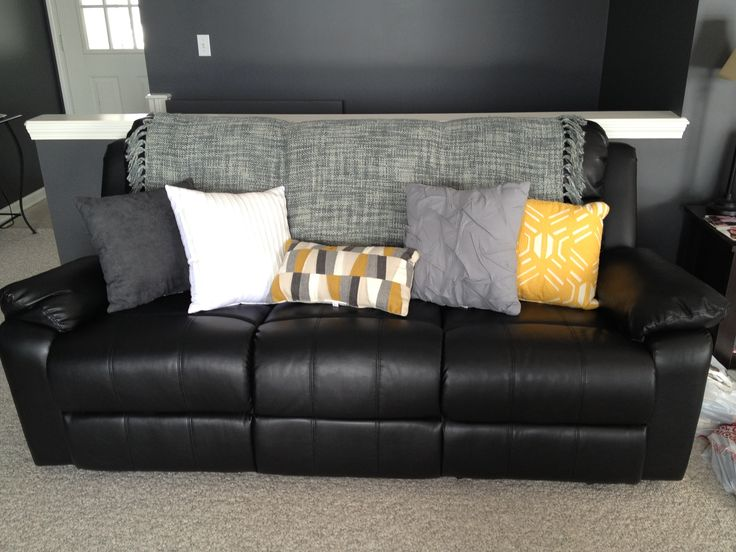 lighten up a black leather couch with bright pillows and a throw
