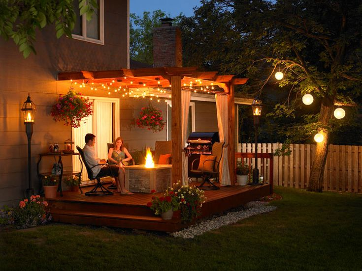A fire pit is a must....I love the lighting to the right and the fabric hanging from the posts make it so soft....