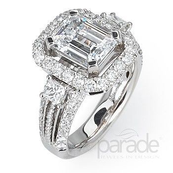 An emerald-cut diamond is enhanced by surrounding brilliant diamonds and twists of golden cable.