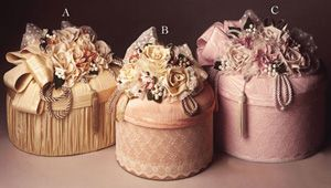 Elegant hat boxes made of fine fabrics adorned with luscious silk floral fabrics with tassels and pearls.