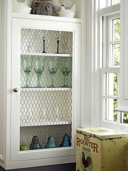 In this cottage kitchen, farmhouse-style chicken wire replaces glass on some cabinets. | Photo: Laura Moss