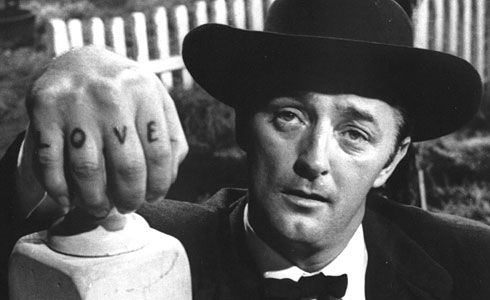 """In 1955 Charles Laughton stepped behind the camera to direct the """"The Night of the Hunter"""" starring Robert Mitchum who also stepped out of his regular guy/bad boy persona to portray genuine evil. From a script by James Agee this haunting film was too strange to be popular when it was new, but its themes of greed and violence against women resonate more strongly with every passing year."""