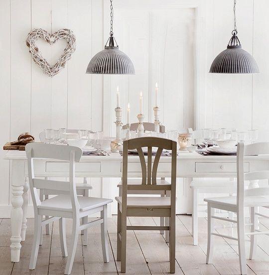 Gezellige witte eetkamer met verschillende stoelen en mooie lampen.