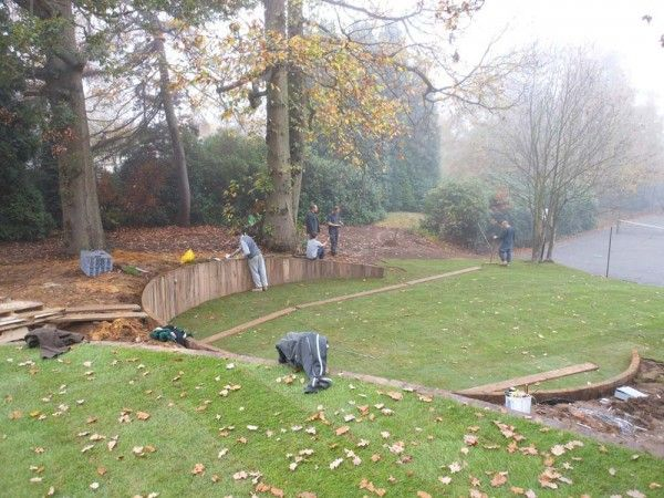 Curved retaining wall in progress railways sleepers for Curved garden wall ideas