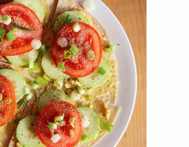Toasted rice tortilla topped with homemade hummus, cucumbers, tomatoes ...