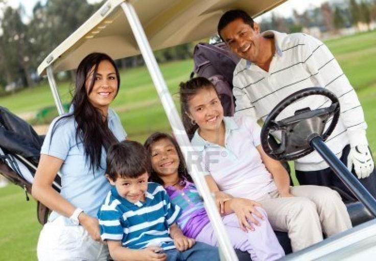 Beautiful family portrait in a cart at the golf course Stock Photo