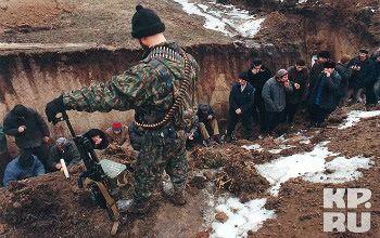Российский военный рассматривает в яме пленных кавказцев