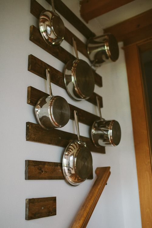 pots and pans hanging on wall organization is key