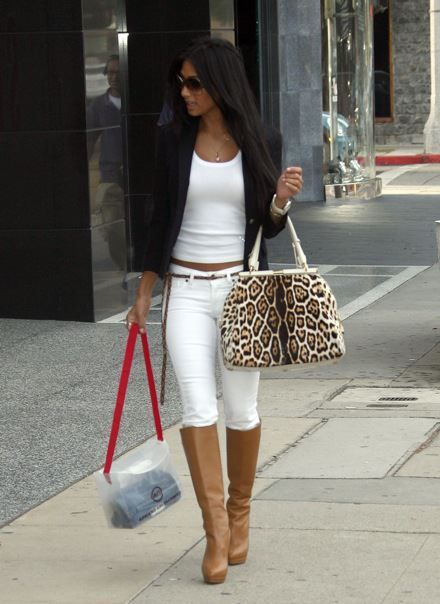 Tight white shirt, tight white pants, brown boots, black jacket, animal print purse and ......clear plastic thing.  WTF?