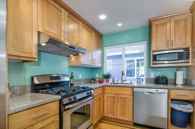 teal colored kitchen walls with natural wood cabinets