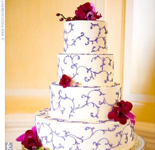 Piped with a deep purple ivy pattern, the four-tiered buttercream cake was topped with fresh flowers